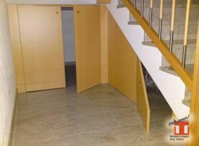 Verkleidung unter einem Treppenaufgang im Treppenhaus mit Falttüren.